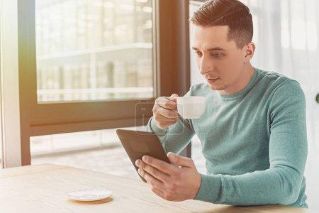 Photo pour Bel homme clouant avec ebook tout en tenant la tasse avec du thé - image libre de droit
