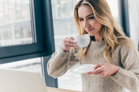 Photo for Attractive woman smiling while holding cup with tea - Royalty Free Image