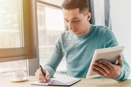Photo for Handsome man studing with digital tablet and writing in notebook - Royalty Free Image