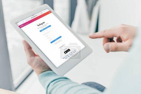 Photo pour Vue recadrée de l'homme tenant tablette numérique avec application instagram à l'écran - image libre de droit