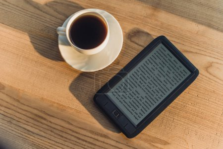 Photo for Black e-book lying near cup with drink - Royalty Free Image
