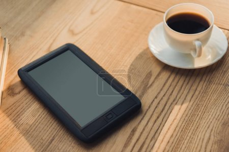 Photo for Ebook with blank screen lying near cup with coffee - Royalty Free Image