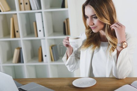 Photo for Cheerful woman holding cup with drink in office - Royalty Free Image