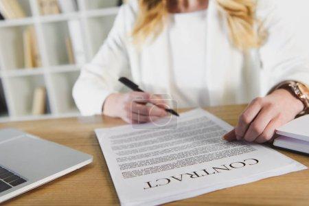 Photo pour Vue recadrée de femme tenant le stylo près de contrat - image libre de droit