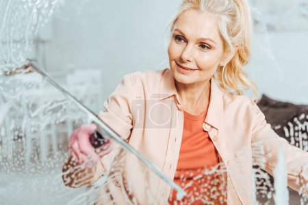 Photo for Senior woman with pony tail cleaning window with glass wiper - Royalty Free Image