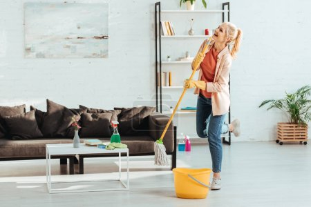 Photo for Laughing senior woman posing on one leg while cleaning floor with mop - Royalty Free Image