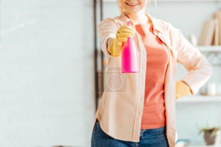 Photo pour Vue recadrée de la femme en gants de caoutchouc tenant bouteille rose - image libre de droit