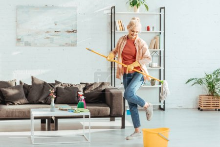 Photo for Gorgeous senior woman dancing while cleaning floor in living room - Royalty Free Image