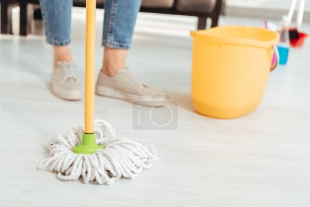 Photo pour Vue recadrée de femme nettoyer le sol avec une vadrouille - image libre de droit