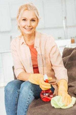 Photo pour Riant senior femme dans des gants de caoutchouc canapé avec vaporisateur et chiffon de nettoyage - image libre de droit