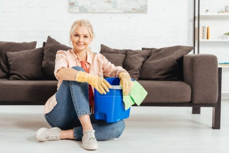 Laughing senior woman sitting on floor and holding bucket with rag