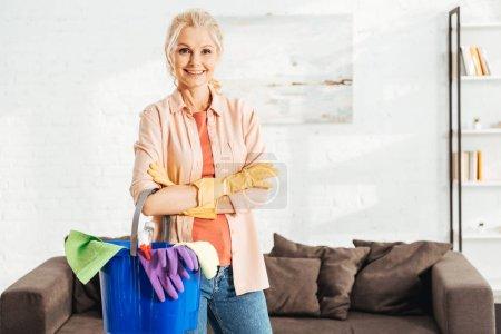 Photo pour Femme âgée riante posant avec les bras croisés et tenant seau avec des fournitures de nettoyage - image libre de droit