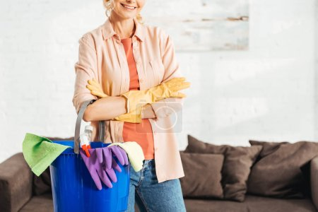 Cropped view of glad woman holding bucket with cleaning supplies
