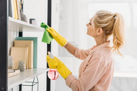 Photo for Senior woman with pony tail cleaning shelves with rag - Royalty Free Image