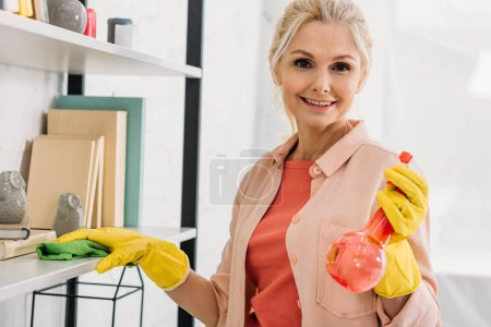 Photo for Smiling senior woman cleaning shelves with spray and rag - Royalty Free Image