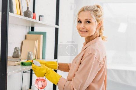 Photo pour Femme senior joyeuse dans les gants de caoutchouc jaune nettoyage des étagères - image libre de droit