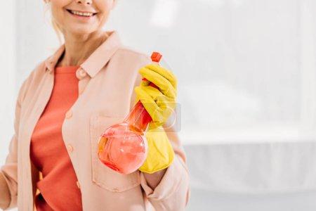Photo pour Vue recadrée de la femme souriante en gant jaune tenant le flacon pulvérisateur - image libre de droit