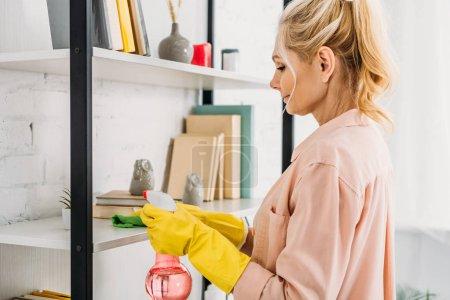 Foto de Mujer rubia en guantes de goma amarillo limpiar los estantes de libro - Imagen libre de derechos