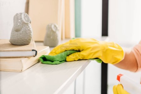 Cropped view of woman in yellow rubber glove cleaning book shelf