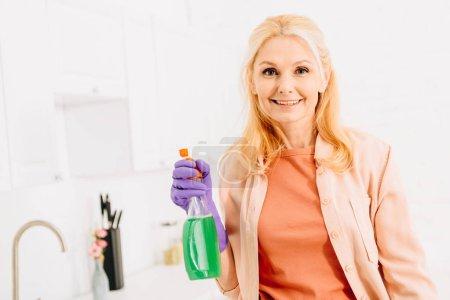 Photo pour Femme âgée excitée posant avec vaporisateur - image libre de droit