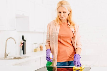 Photo for Blonde senior woman washing kitchen stove with rag and spray - Royalty Free Image