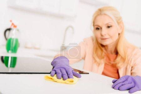Foto de Mujer mayor rubia limpieza cocina estufa con trapo - Imagen libre de derechos