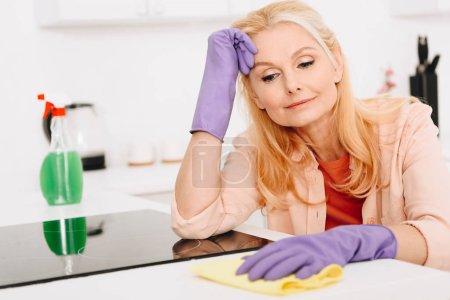 Photo pour Fatigué femme senior dans les gants de caoutchouc nettoyage cuisine - image libre de droit