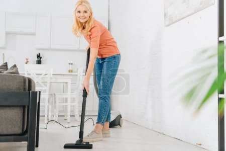 Photo for Cheerful senior woman cleaning floor with vacuum cleaner - Royalty Free Image