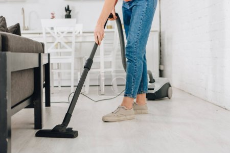 Cropped view of woman cleaning floor with vacuum c...