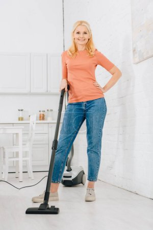 Photo for Joyful blonde woman cleaning house with vacuum cleaner - Royalty Free Image