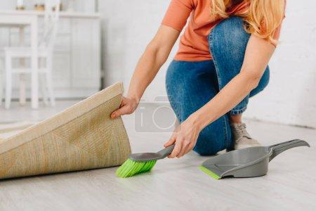 Foto de Recortada visión de mujer sosteniendo la alfombra y piso con cepillo de limpieza - Imagen libre de derechos