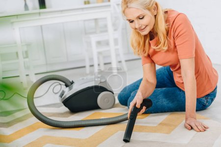 Photo for Smiling blonde woman sitting on carpet and using vacuum cleaner - Royalty Free Image