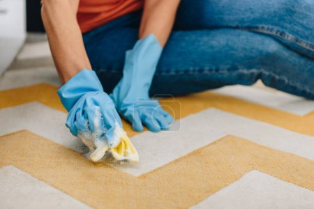 Photo for Cropped view of woman in blue rubber gloves cleaning carpet - Royalty Free Image