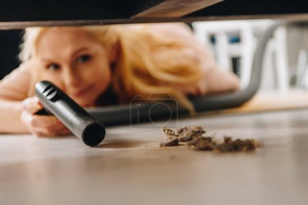 Photo for Senior woman cleaning floor under furniture with vacuum cleaner - Royalty Free Image