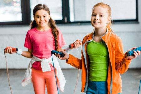Photo pour Enfants heureux posant avec des cordes à sauter dans la salle de gym - image libre de droit