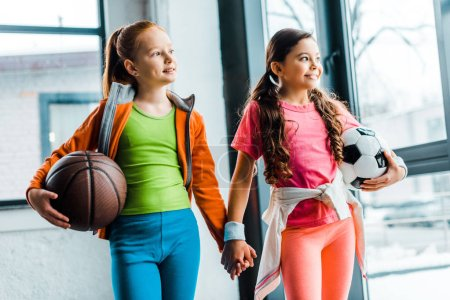 Photo for Blissful kids holding hands while posing in gym - Royalty Free Image