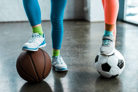 Photo for Cropped view of kids in sneakers posing with balls in gym - Royalty Free Image