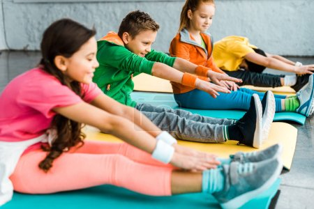 Photo for Kids in bright clothes stretching on fitness mats - Royalty Free Image