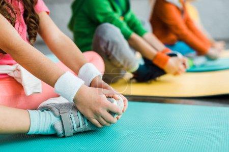 Vista recortada de niños estirándose en colchonetas de fitness
