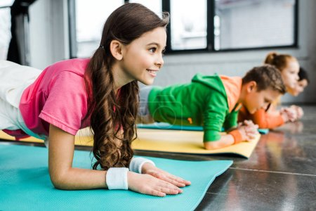 Photo for Children doing plank exercise on fitness mats in gym - Royalty Free Image