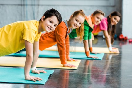 Photo pour Joyeux enfants faire de l'exercice de la planche et en regardant la caméra - image libre de droit