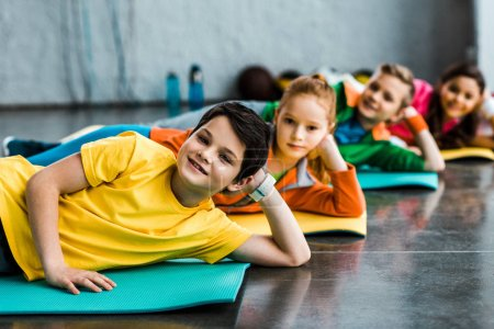 Joyful kids lying on fitness mats and looking at camera