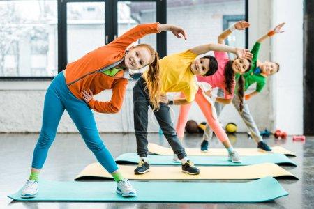 Photo pour Souriant enfants préadolescents faire de l'exercice sportif ensemble - image libre de droit