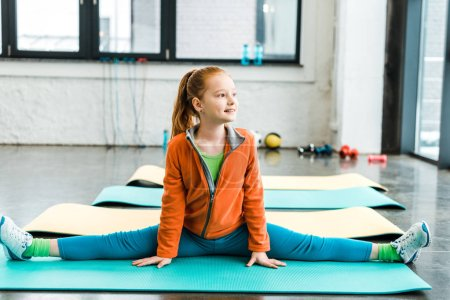 Photo for Dreamy kid with pony tail doing twine in gym - Royalty Free Image