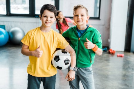 Photo for Boys with soccer ball posing with thumbs up - Royalty Free Image
