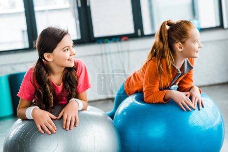 Photo pour Joyeux enfants gisant sur les boules de remise en forme dans la salle de gym et à la recherche de loin - image libre de droit