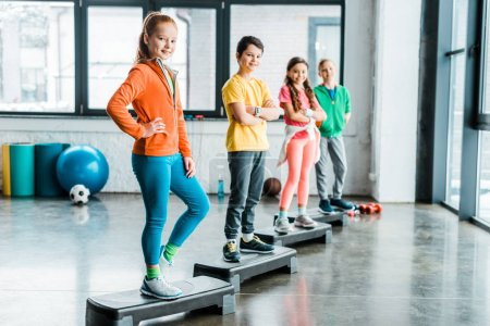 Adorable kids standing on step platforms in gym