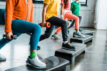 Photo for Cropped view of kids with dumbbells training with step platforms - Royalty Free Image
