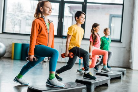 Photo for Preteen kids training with dumbbells and step platforms - Royalty Free Image