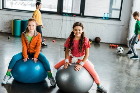 Photo pour Enfants posant avec le sourire assis sur des boules de fitness - image libre de droit